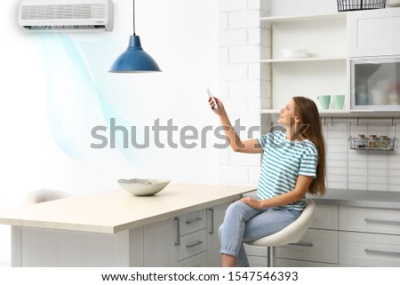 Young woman with air conditioner remote control at home #1547546393