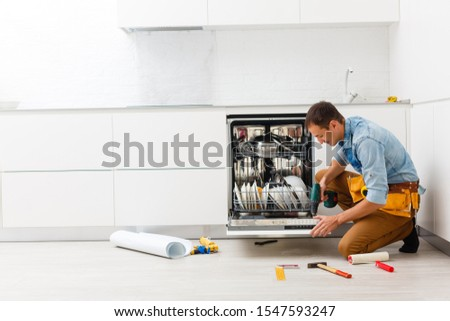 Handsome professional plumber doing sink reparation. Contractor. #1547593247