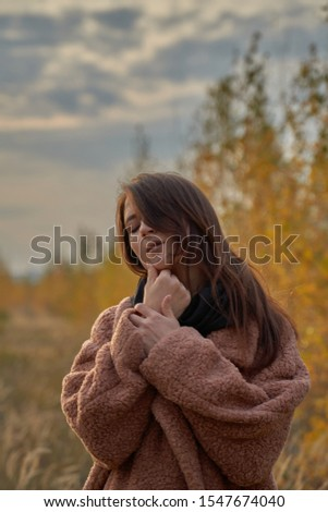 Portrait of a sensual girl in a coat in the fall forest, touching her face. #1547674040