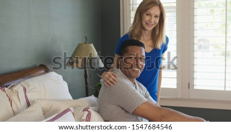 Portrait of African American Man and Caucasian woman senior couple in bedroom smiling at camera. Happy husband and wife at home getting ready for the day #1547684546
