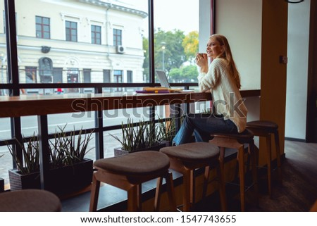 Lovely joyous woman in casual dress relaxing in a local cafe #1547743655