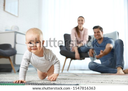 Adorable little baby crawling near parents at home #1547816363