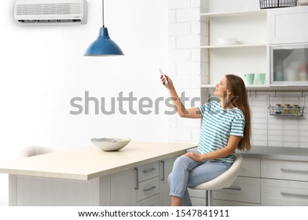 Young woman with air conditioner remote control at home #1547841911
