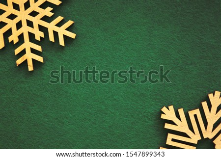 Christmas Eve and Happy New Year flat lay background.Handmade decorative backdrop for winter holidays poster.Green texture,rustic wooden snowflakes in closeup.Empty space for text in center of image