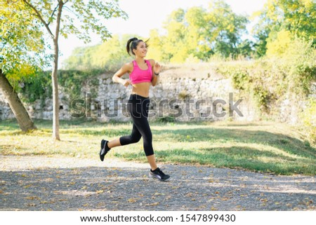 Sport girl is running in park and smiling #1547899430
