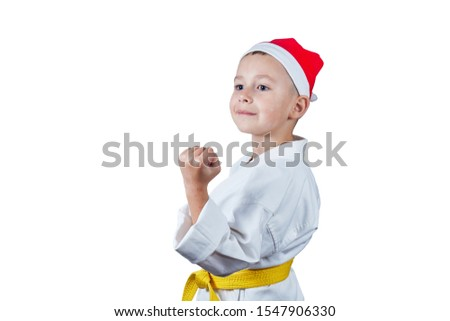 In karate stance little athlete in karategi and santa claus hat Royalty-Free Stock Photo #1547906330
