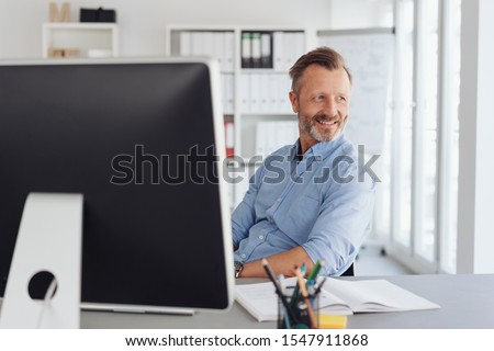 Relaxed businessman watching in amusement as he sits back in his chair looking back through an office window #1547911868