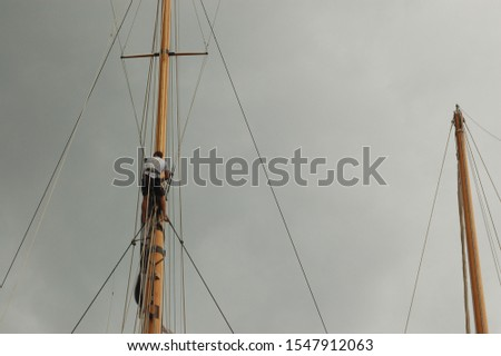Masts of wooden sailing boats, spreaders, shrouds. A sailor is climbing up on a mast. A cloudy sky.  Race at Saint-Tropez, Cote d'Azur, France. #1547912063
