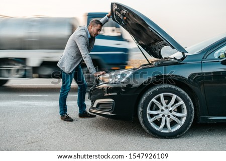 Elegant middle age business man trying to fix car breakdown or engine failure and waiting for towing service for help car accident on the road. Roadside assistance concept. #1547926109