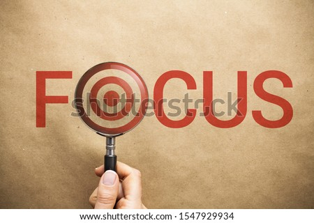 Woman hand holding magnifying glass over the word focus written on paper background. Target symbol in the middle of magnifier. Correct focus leads to targeted success. #1547929934