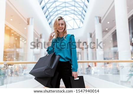 Black Friday. Discounts. Sales. Shopping A girl with packages and shopping smiles and enjoys new clothes. Black paper bags in hands on a blurred background of a shopping center. #1547940014