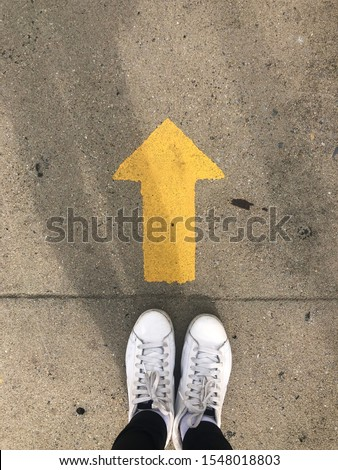 Yellow straight arrow sign and white shoes. Straight direction concept. Journey concept   Royalty-Free Stock Photo #1548018803