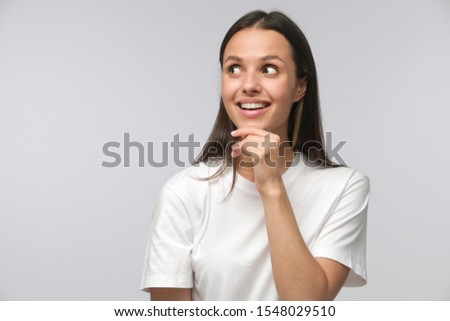 Attractive positive woman looking aside and dreaming. Pleased smiling female thinking with dreamy expression, isolated on gray background #1548029510