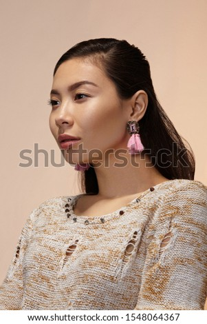 Medium close-up shot of a dark-haired Asian lady in a beige mottled pullover with earrings made as a pink square gem in a bronze tracery setting with crystals and pink thread tassels.   #1548064367