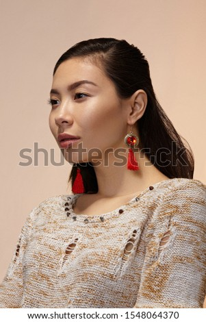 Medium close-up shot of a dark-haired Asian lady in a beige mottled pullover with bronze hook earrings with a circular flat with geometric ornaments, red faceted gem and red thread tassels.  #1548064370