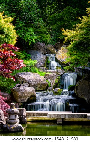 Waterfall long exposure vertical view with maple trees in Kyoto Japanese green Garden in Holland Park green summer zen lake pond water in London, UK #1548121589