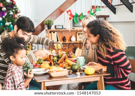 Thanksgiving Celebration Tradition Family Dinner Concept.family having holiday dinner and cutting turkey.Young black adult woman and her daughter happy. #1548147053