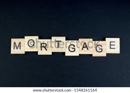 mortgage- word composed fromwooden blocks letters on black background, copy space for ad text #1548261164