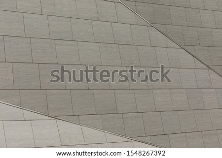 Close-up of grey concrete tiled wall. Three shades of gray on ceramic surface. #1548267392