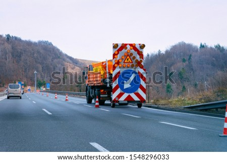 Truck carrying arrow down left reflective direction road sign in highway. Roadwork service signal. Narrow lane traffic indicator.