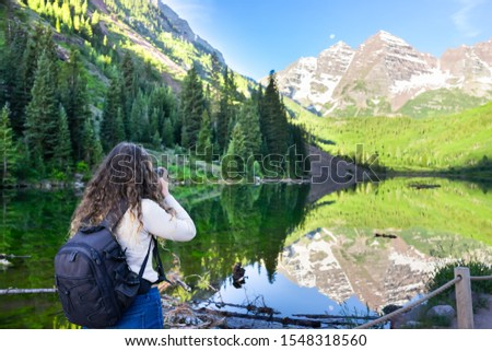 Maroon Bells in Aspen, Colorado in July 2019 summer and mirror reflection at sunrise with woman photographer back taking picture photo