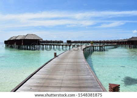 Villas over the atoll blue ocean and clear sky #1548381875
