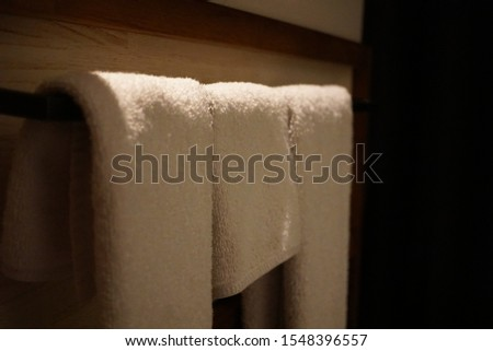 The hanging white towel in the bathroom in dark color tone #1548396557