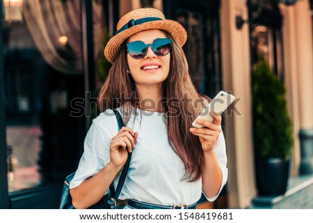 Young stylish woman using phone walking on the street, travel with backpack, straw hat, wearing trendy outfit. #1548419681
