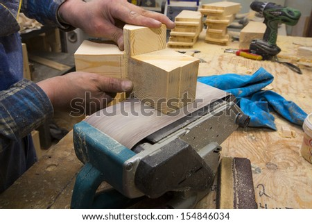 Man polishing wood with sandpaper in workshop #154846034