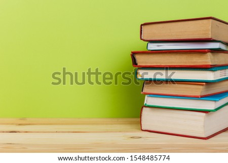 Simple Simple composition of many hardback books, unprocessed books on a wooden table and a green background. back to school. Copy space. Education. #1548485774
