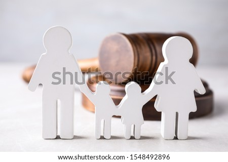 Figure in shape of people and wooden gavel on light table. Family law concept #1548492896