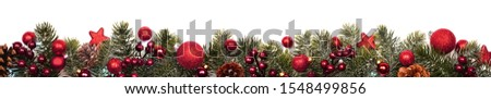Long Christmas border banner of red ornaments and branches isolated on a white background