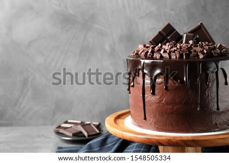Freshly made delicious chocolate cake on grey background Royalty-Free Stock Photo #1548505334