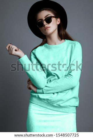 Beautiful fashion model with glasses and black hat in studio with bright turquoise jumper and skirt #1548507725