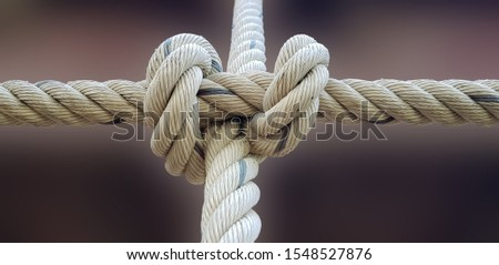 Close-up of rope knot line tied together with bridge background. White rope tied in a knot for adventure.Rope, tie a knot tied to a mesh of metal poles for children to climb. Royalty-Free Stock Photo #1548527876