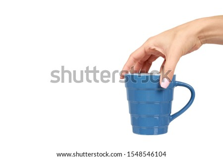 Hand with blue ceramic cup, mug for coffee and tea, kitchen pottery. Isolated on white background. Copy space template, mockup. #1548546104