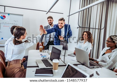 Human resources concept. New accepted worker gives high five to his new colleague. First day on work #1548577937