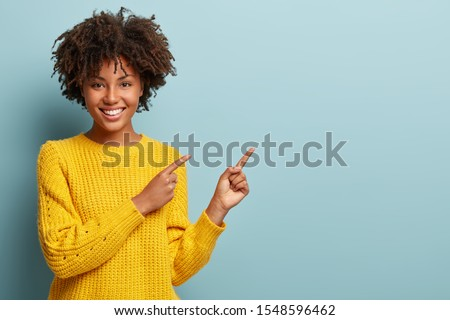 Cheerful Afro woman points away on copy space, discusses amazing promo, gives way or direction, wears yellow warm sweater, has pleasant smile, feels optimistic, isolated over blue background #1548596462