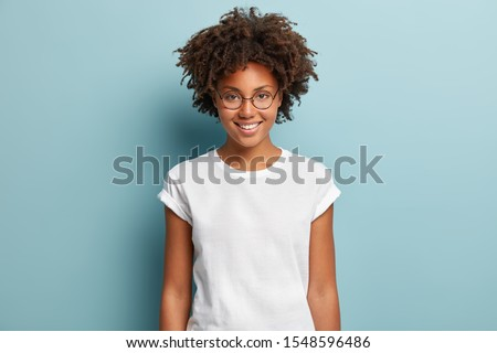Waist up shot of happy curly woman with toothy smile, wears optical glasses and casual solid white t shirt, expresses good emotions, enjoys nice day, isolated over blue background. Face expressions Royalty-Free Stock Photo #1548596486