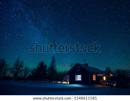 Cottage against the night sky with the Milky Way and the arctic Northern lights Aurora Borealis in snow winter Finland, Lapland #1548611585