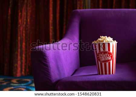 Striped paper bucket of fresh popcorn placed on soft vibrant violet armchair during showtime in movie theater #1548620831