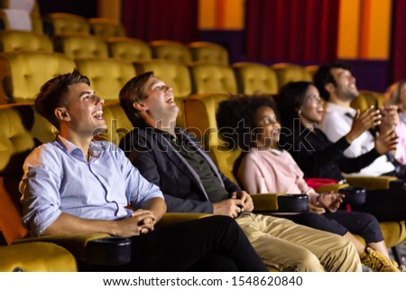 Laughing casual men sitting on soft chairs and laughing while watching funny moving during showtime in movie theater #1548620840