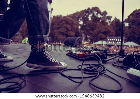 Guitarist perfroming live on hardrock concert stage outdoor.Feet of bass guitar player playing solo part on rock festival in summer.Punk band perform on scene,focus on old dirty sneakers of musician #1548639482