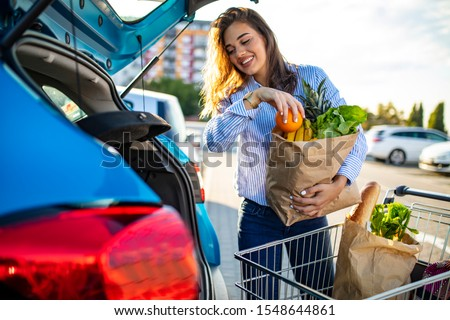 Woman packing shopping bags into a trunk of her car. Young woman with groceries at parking lot. Young women packing groceries from supermarket in car trunk. Woman holding groceries in reusable bag #1548644861