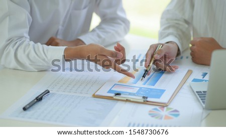 Business office staff are analyzing data graphs to summarize annual results. #1548730676