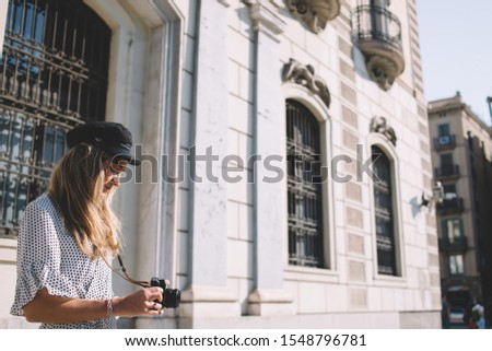 Side view of attractive Caucasian hipster girl dressed in stylish apparel checking pictures on modern technology during time for exploring Barcelona city, beautiful female tourist editing photo