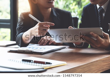 Fund managers team consultation and discuss about analysis Investment stock market by digital tablet. Royalty-Free Stock Photo #1548797354