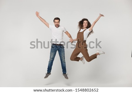 Overjoyed millennial couple have fun in white grey photo studio shooting for family picture together, excited young man and woman entertain jump holding hands, posing looking at camera #1548802652
