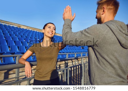 A young couple of athletes raised their hands up in the morning at dawn. #1548816779