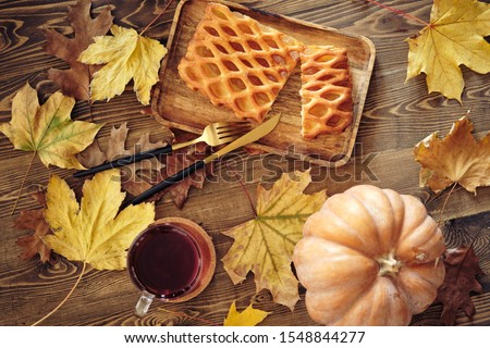 sweet Apple pie with tea on the background of a wooden surface strewn with dry autumn leaves #1548844277